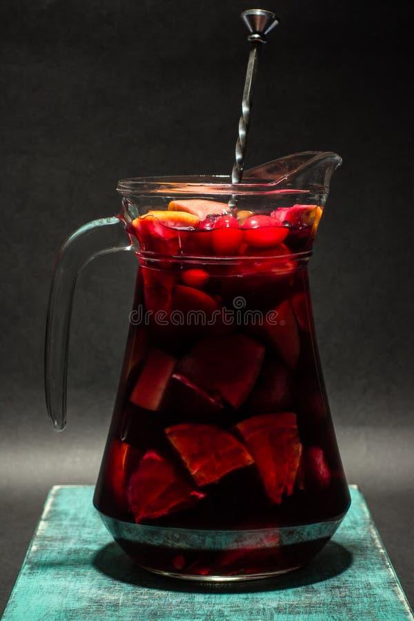 大瓶子用夏天果子柠檬水,红色桑格里酒,演播室照片 免版税库存图片
