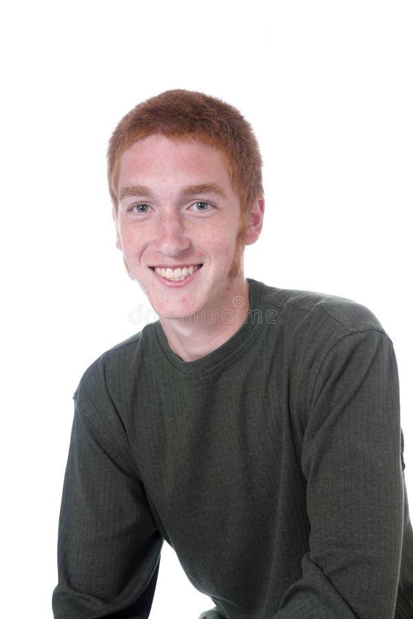 大男孩朝向少年红色的微笑 免版税库存照片