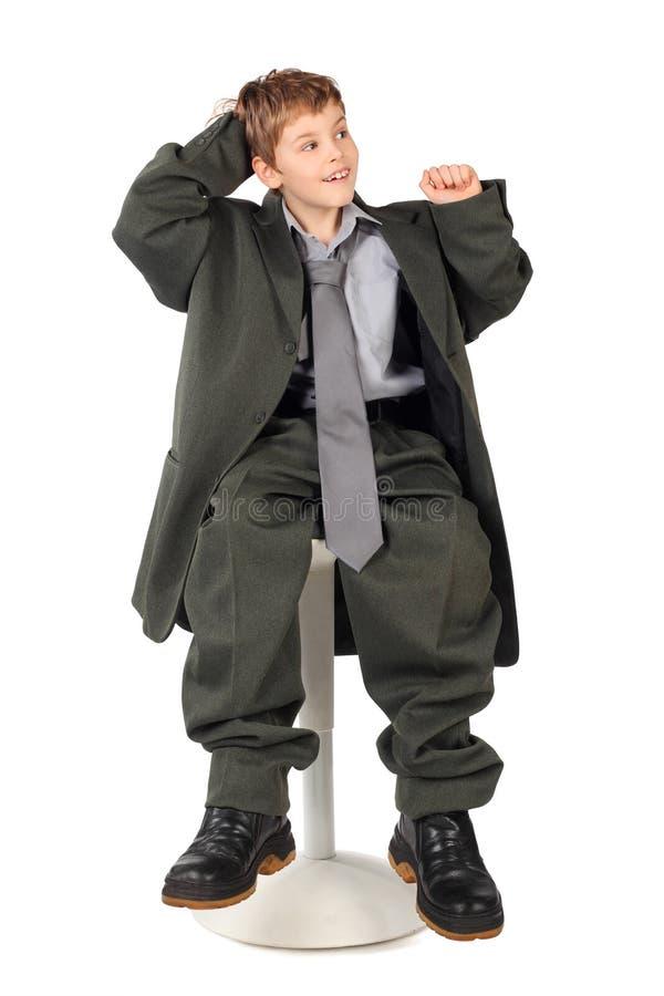 大男孩椅子查出人s坐的诉讼 免版税库存图片