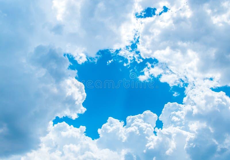 大白色云彩和光线在云彩后与蓝天 免版税库存照片