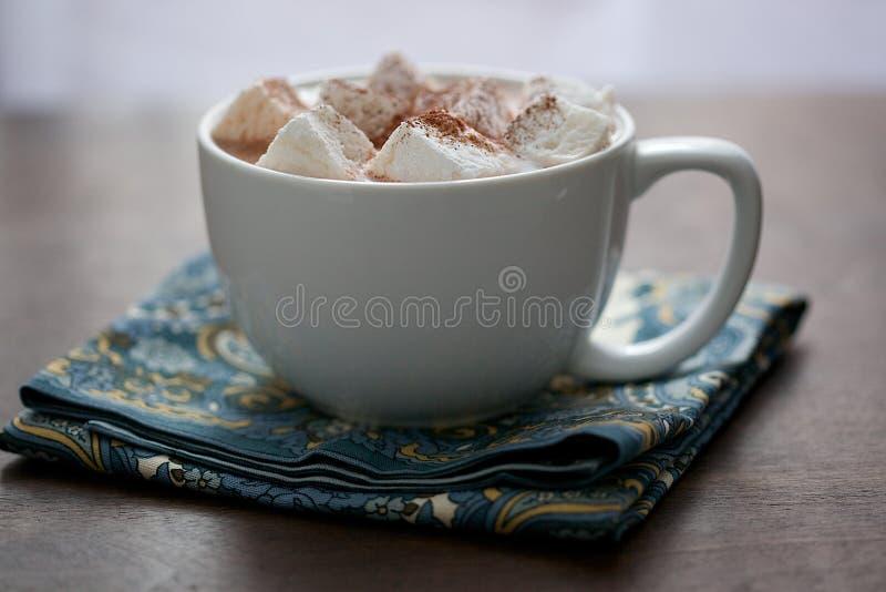 大白色杯子用蛋白软糖和热的可可粉在餐巾 库存照片