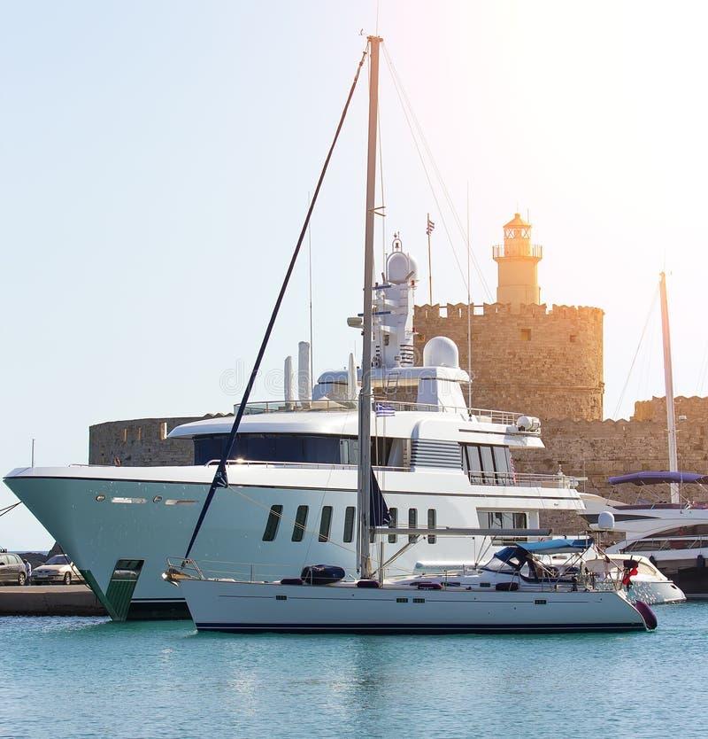 大白色现代马达superyacht在罗得岛希腊港口城市 免版税图库摄影