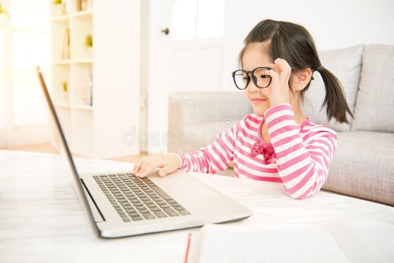 戴大眼镜的女孩使用她的膝上型计算机 免版税图库摄影