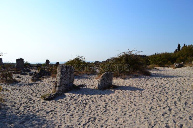 大石头在沙子驱散了在一个热的夏天早晨 库存照片
