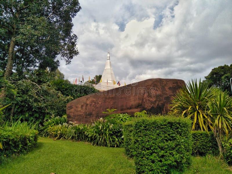 大石头的白色塔与与天空的绿色草坪前景 免版税库存照片