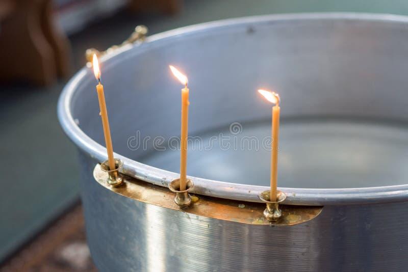大碗一个婴孩的洗礼的水有蜡蜡烛的 正教 希腊天主教徒 三个蜡烛对边的烧伤 免版税库存图片
