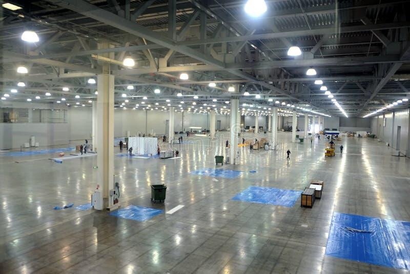 大空的仓库里面与一套高顶和人为照明设备的工厂厂房的 免版税库存照片