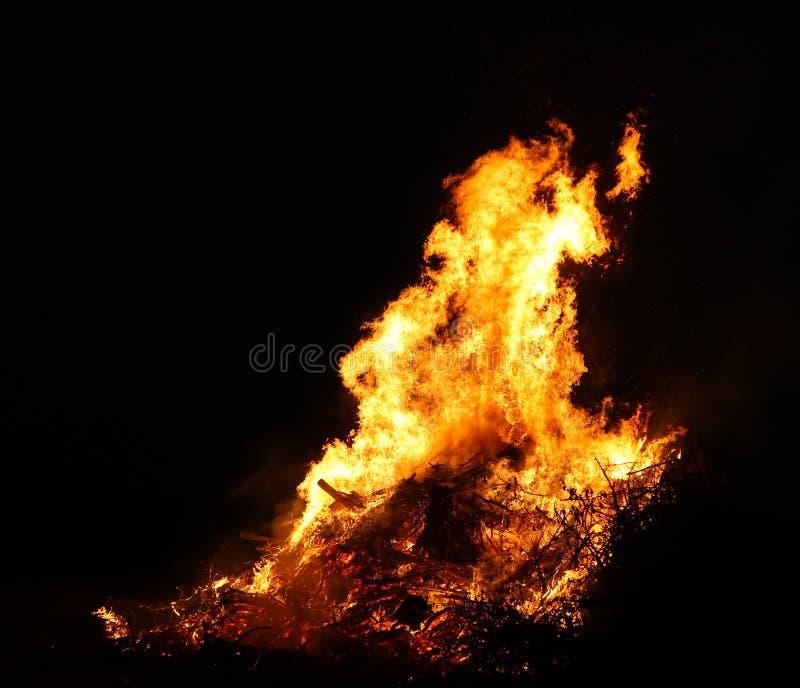 大篝火,烧和发光与软的火焰,闪耀飞行的agains黑暗的天空 发光的木剪影 沃普尔吉斯之夜 库存图片