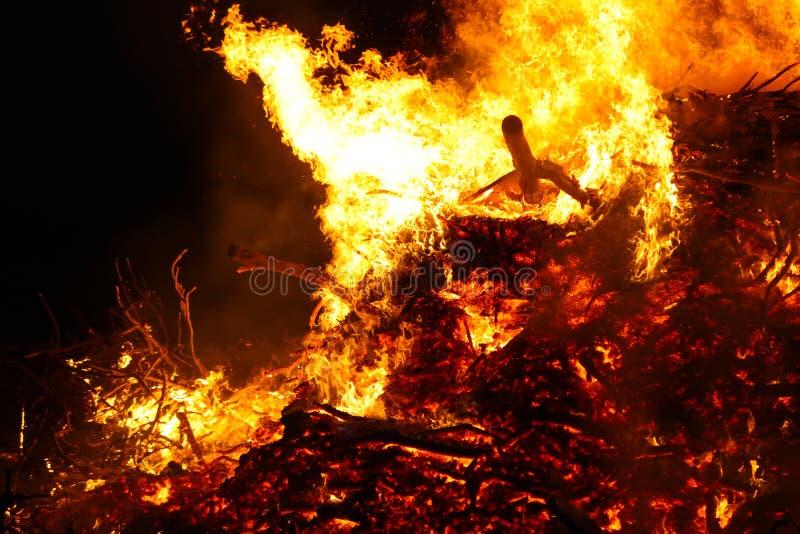 大篝火,烧和发光与软的火焰,闪耀飞行的agains黑暗的天空 发光的木剪影 沃普尔吉斯之夜 图库摄影