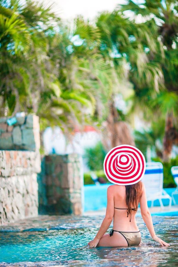大红色帽子的年轻美丽的妇女享受在安静的游泳池的暑假 库存图片