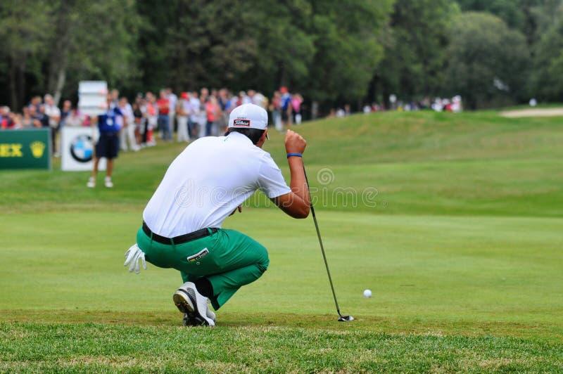 大约正确的线在绿色蹲的9月未知的高尔夫球运动员集中寻求的都灵意大利 免版税库存照片