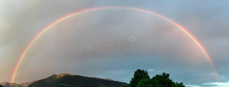 大美丽的彩虹在阴暗天空成拱形 库存照片