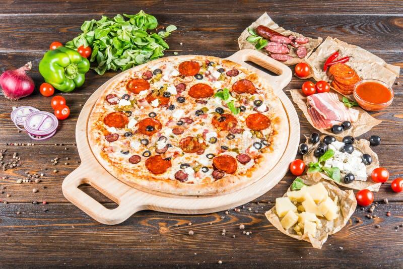大肉比萨用烟肉、香肠、蒜味咸腊肠、意大利辣味香肠和oliv 免版税库存图片