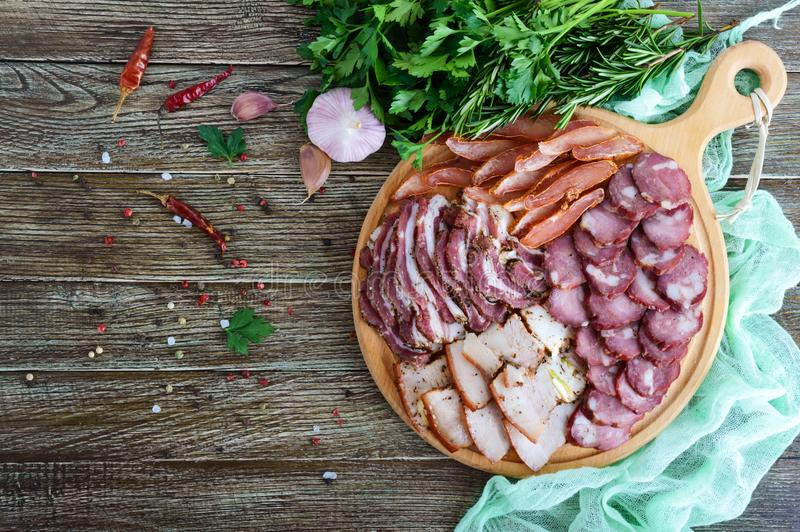 大肉集合 自创熏制的猪肉牛肉香肠,盐味的烟肉, basturma砍了在一个木板的切片用香料和草本 库存图片