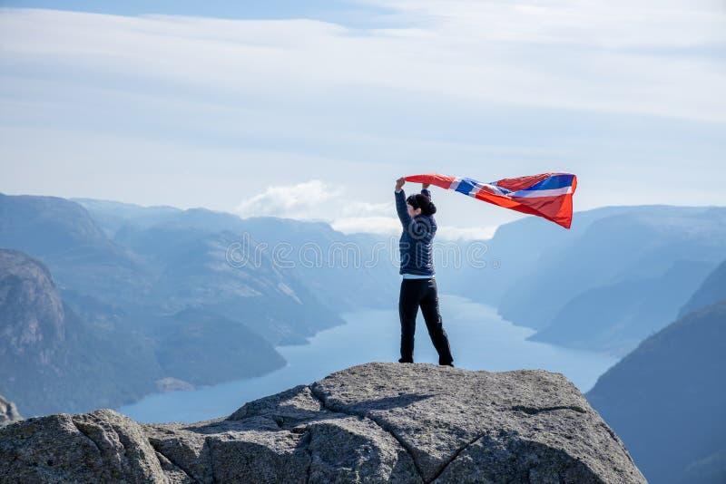大自然背景上挥舞挪威国旗的妇女 免版税库存照片