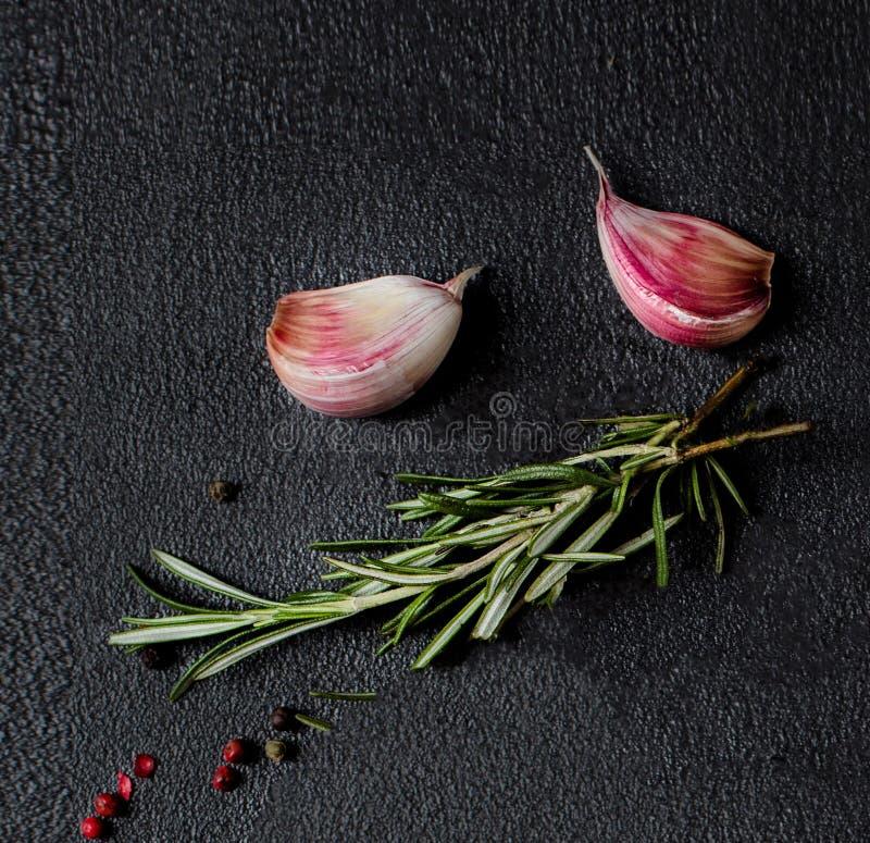 大蒜、迷迭香草本和胡椒在黑具体背景,顶视图 传统烹调食品成分意大利的薄饼 库存图片