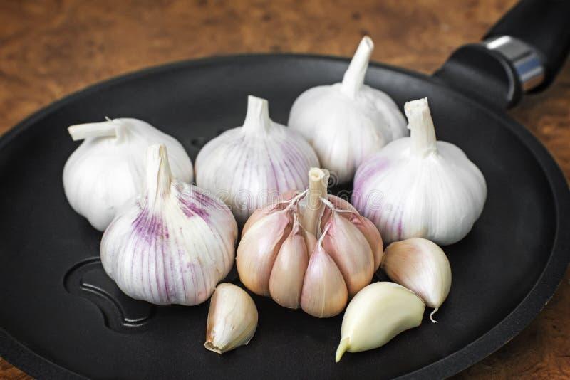 大蒜和一个煎锅在桌特写镜头 图库摄影