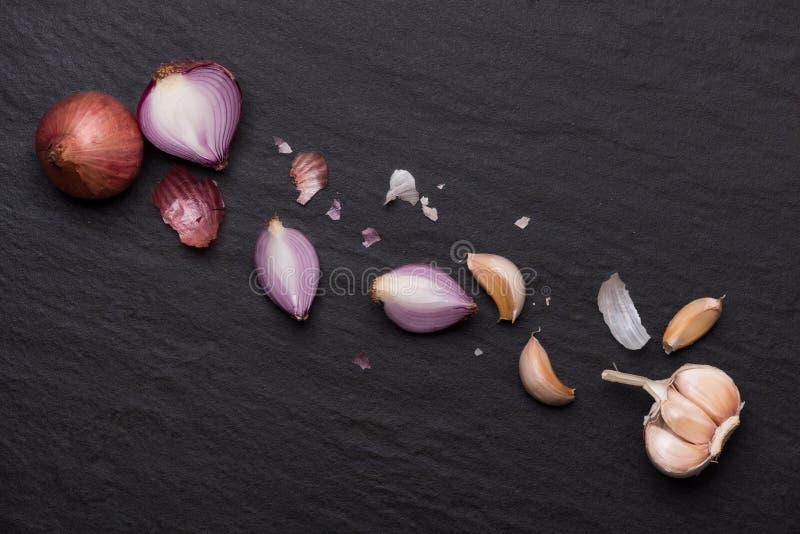 大蒜和葱在黑石桌上 免版税库存照片