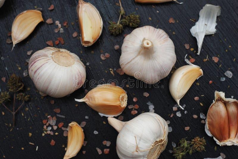 大蒜用在黑暗的背景的香料 食谱和食物配制的食品成分 盐和纸 库存照片