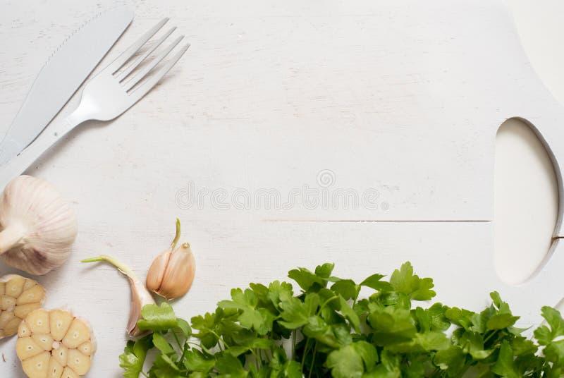 大蒜荷兰芹在一个木白色古色古香的葡萄酒切板绿化 烹调食物 吃健康 荷兰芹和大蒜 免版税图库摄影