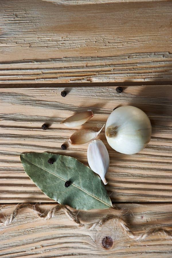 大蒜,葱,月桂叶,在一张木桌上的黑胡椒 背景许多饺子的食物非常肉 garlics 切的大蒜,拨蒜,大蒜电灯泡 库存照片