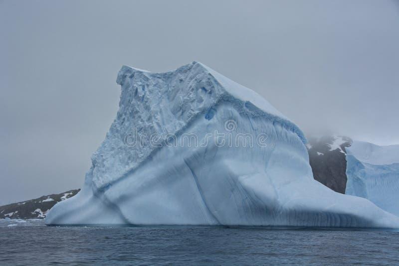 大蓝色冰山在一阴沉的天在南极洲 图库摄影