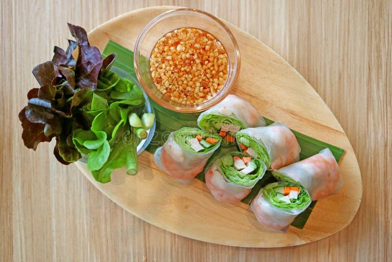 大虾和新鲜蔬菜春卷服务用在一块木板材的蔬菜沙拉 图库摄影
