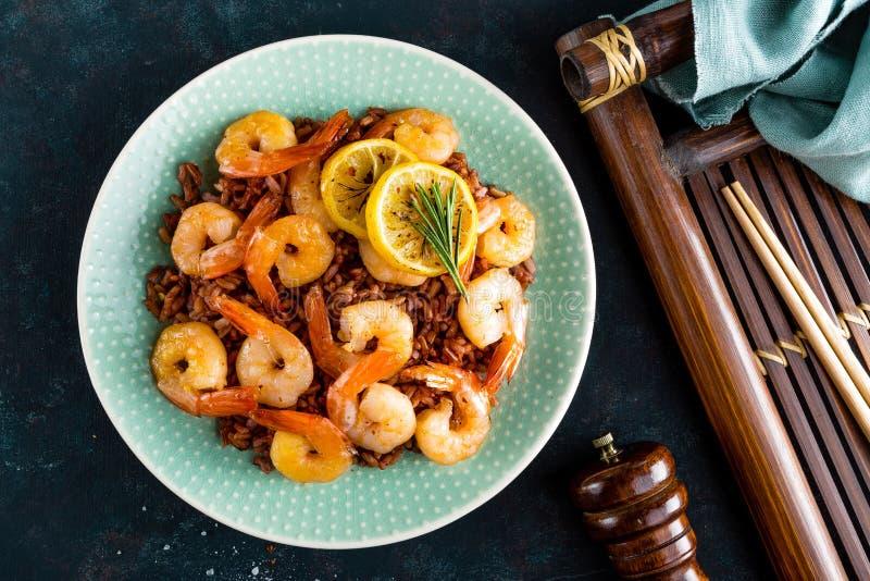 大虾在格栅烤了并且煮沸了在板材的糙米 烤虾,大虾用米 海鲜 亚洲烹调 顶视图 免版税库存照片