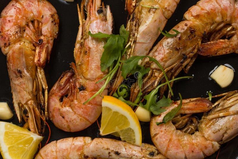 大虾虾用大蒜、柠檬、香料和意大利欧芹在白色被绘的土气木头,选择的焦点的一个黑平底锅装饰, 免版税图库摄影