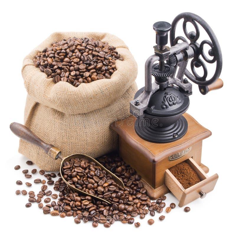 大袋与在白色隔绝的减速火箭的研磨机的咖啡豆 库存照片