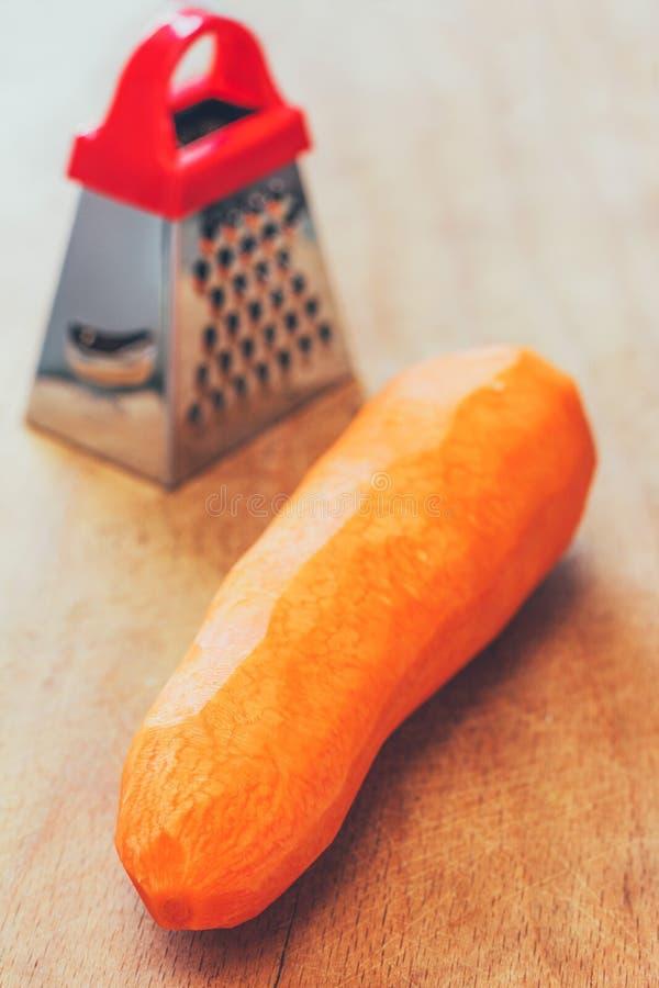 大被剥皮的红萝卜和一台小磨丝器 库存照片