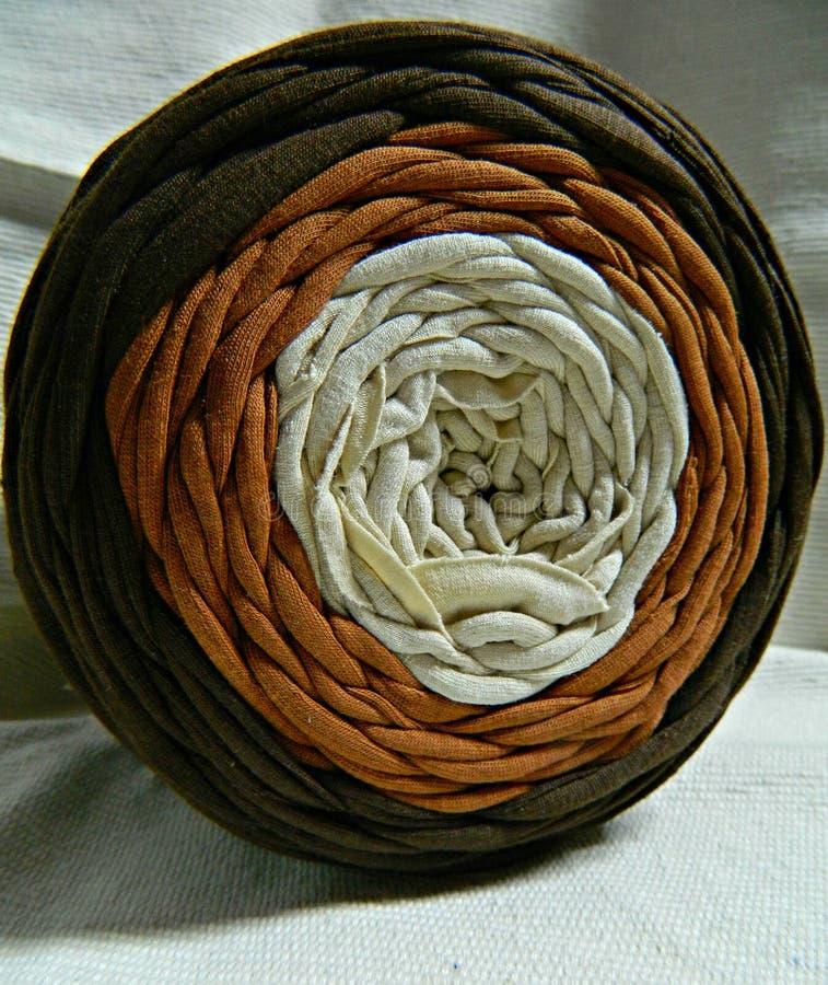 大被编织的毛线卷三色:棕色,茶黄和奶油色 免版税库存照片