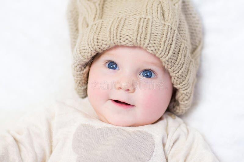戴大被编织的帽子的可爱的新出生的婴孩 免版税图库摄影