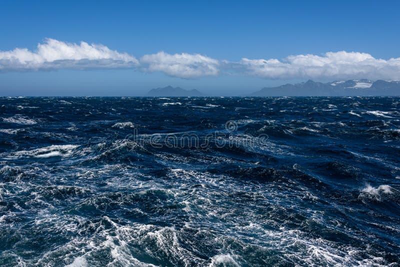 大西洋和遥远的山,浪潮起伏的水,与白色云彩的镇静天空蔚蓝看法  免版税库存图片