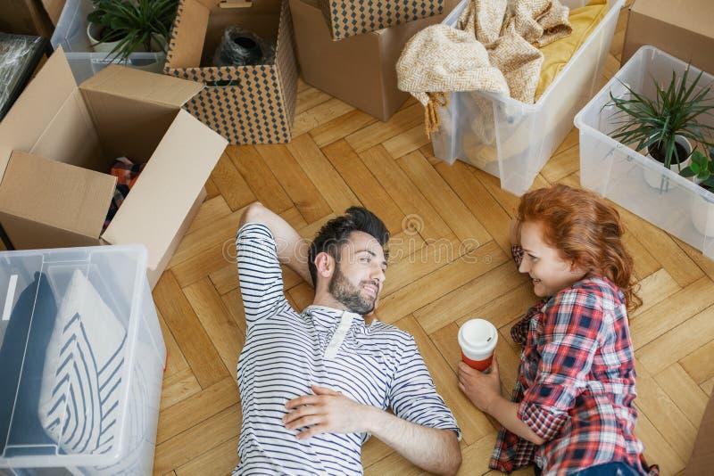大角度在地板上的愉快的夫妇在箱子和材料旁边,当移动在时 免版税图库摄影