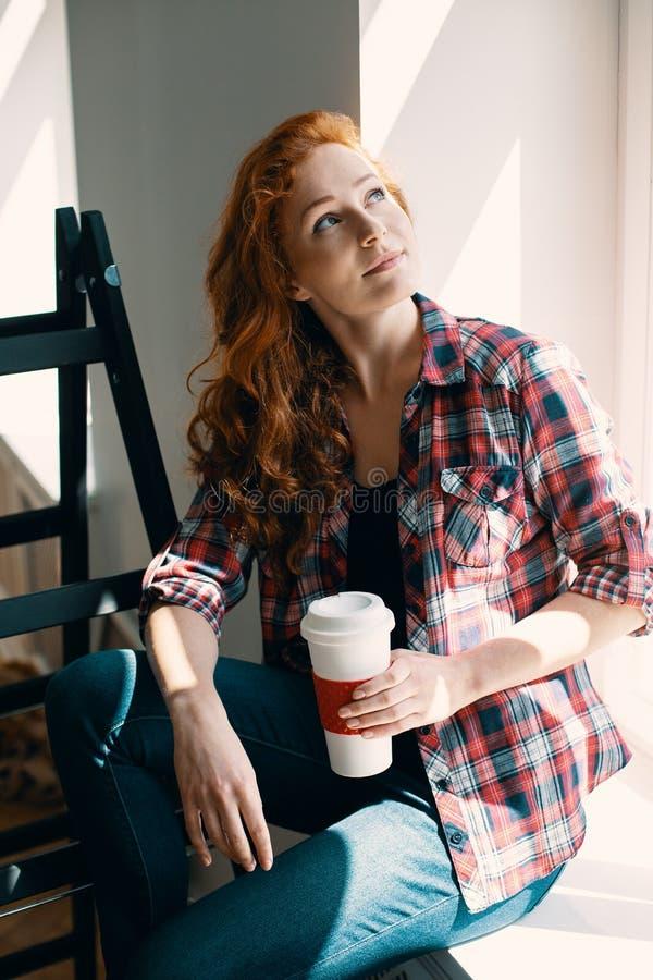 大角度在有咖啡的红发妇女在家在整修时 库存图片