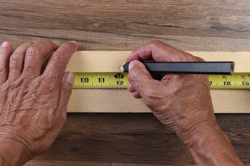 大角度特写镜头使用卷尺的木匠手标记在委员会的插队 库存照片