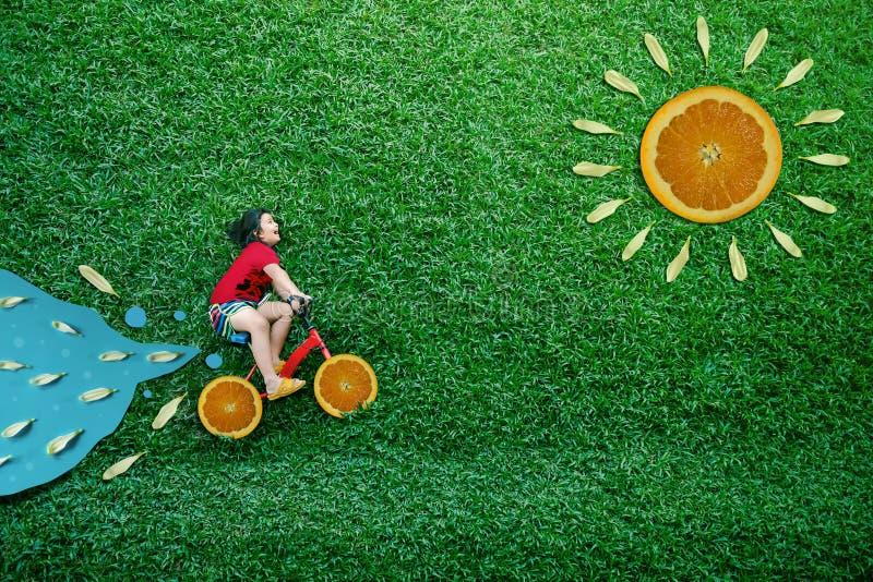 大角度看法愉快的亚洲孩子 自行车的女孩在绿色草坪放下在夏天好日子 想象力和创造性 图库摄影