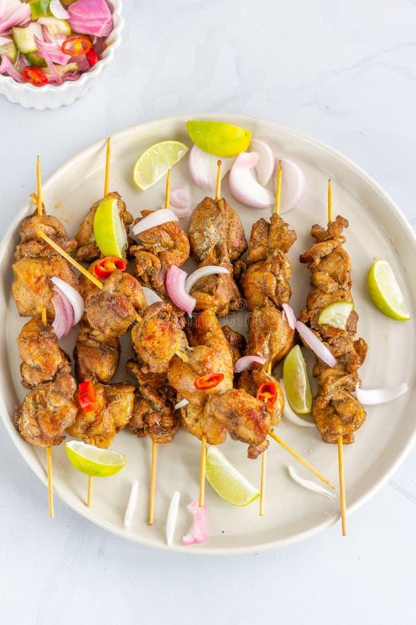大角度观点的与花生调味汁和沙拉普遍的印度尼西亚和泰国的鸡Satay开胃菜 泰国食物,东方烹调, 免版税库存照片