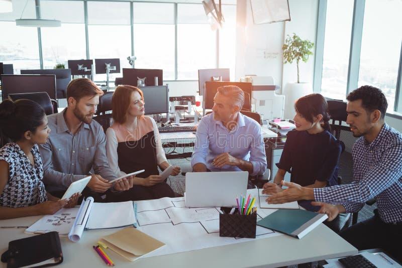 大角度观点的创造性的企业同事谈论在书桌附近 免版税库存照片