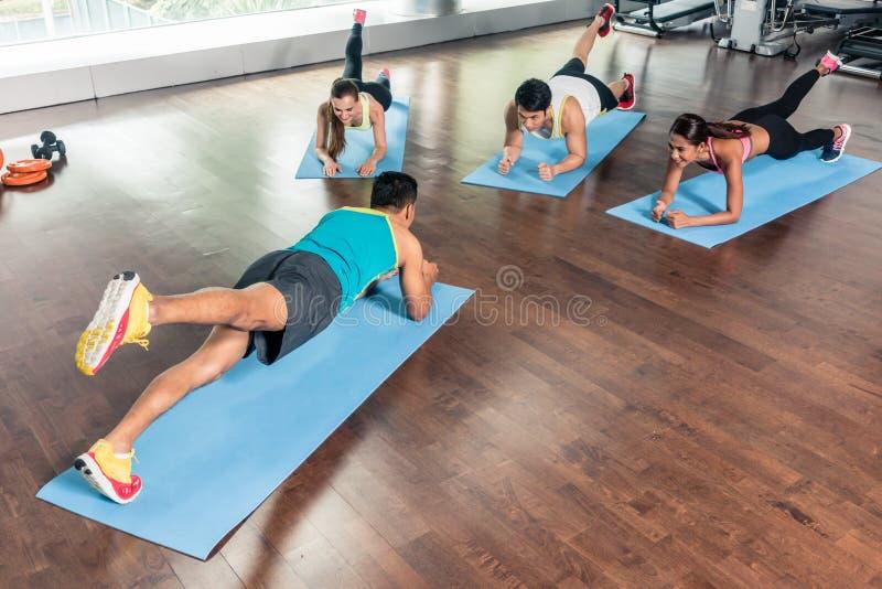 大角度观点的在小组女子柔软体操期间的健身辅导员 图库摄影