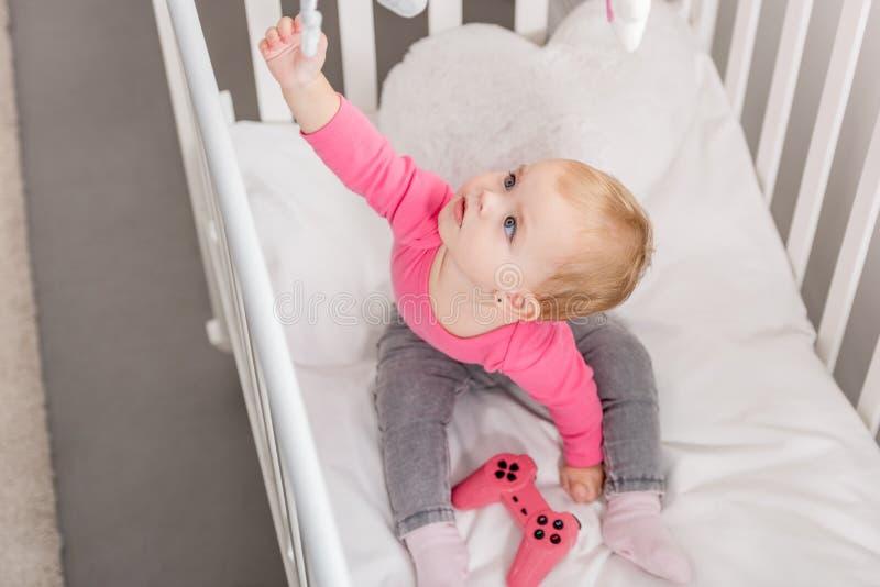 大角度观点的在拿着在小儿床的桃红色衬衣的可爱的孩子桃红色控制杆和 库存照片