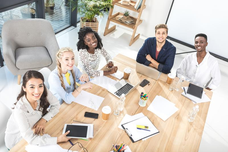 大角度观点的多文化小组看照相机的商人,当坐在桌上时 库存图片