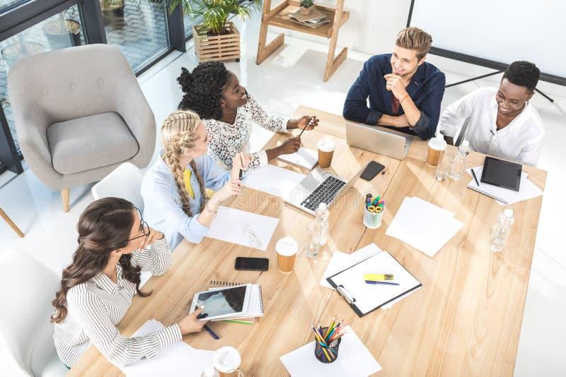 大角度观点的多文化小组谈论的商人工作 免版税库存照片