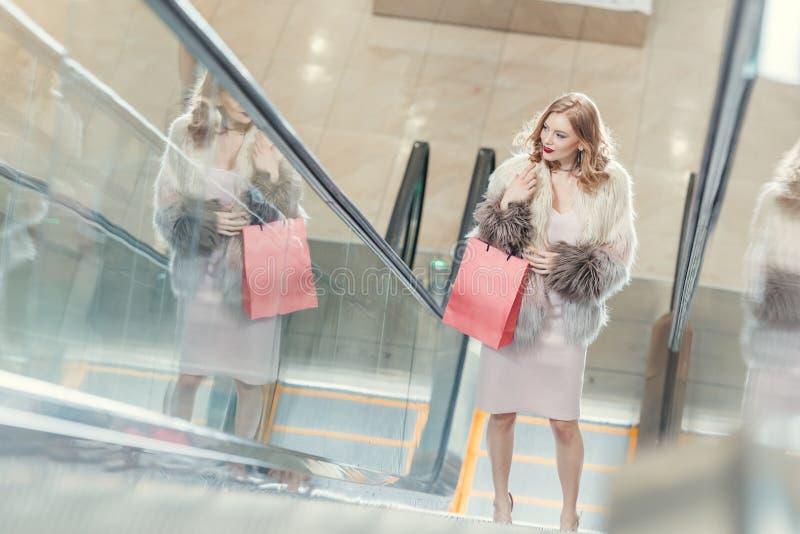 大角度观点的有购物袋的时髦的妇女在自动扶梯 库存照片