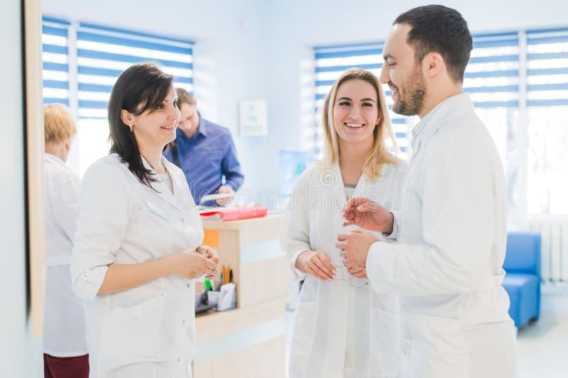 大角度观点的白色外套的三位医生有交谈在医院大厅 免版税图库摄影