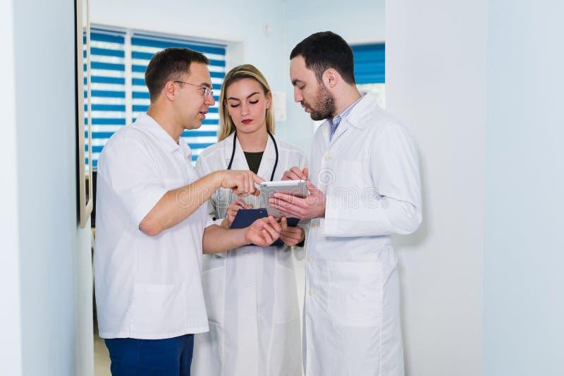 大角度观点的白色外套的三位医生有交谈在医院大厅 库存图片