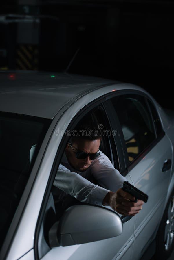 大角度观点的瞄准被枪的太阳镜的男性密探 库存图片