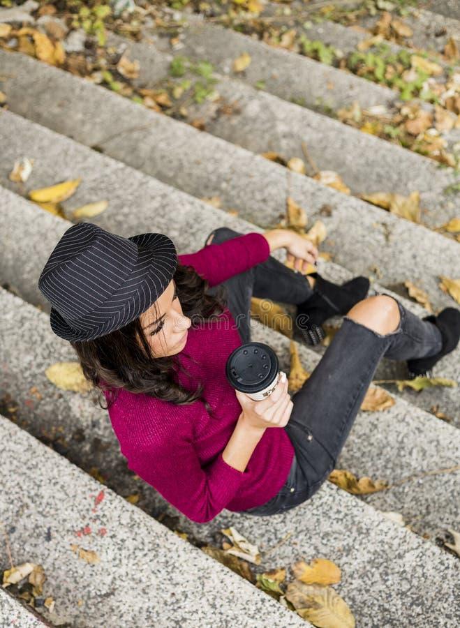 大角度观点的红色毛线衣的愉快的年轻女人有纸杯的 库存图片