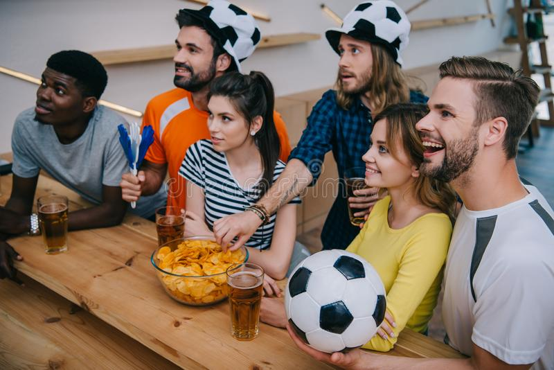 大角度观点的足球帽子的朋友喝啤酒和观看足球赛的微笑的多文化小组  库存图片